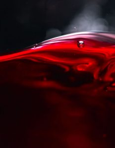 Extreme close-up of a swirl of red wine in a glass