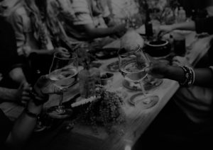 Black and white pic of people in conversation around a table